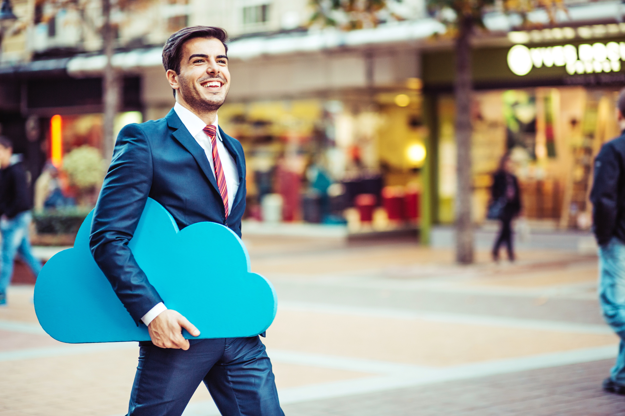 Young businessman walking on the street carrying a big blue cloud
